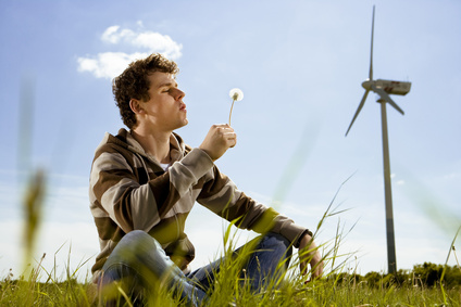 Junge mit Pusteblume vor Windrad